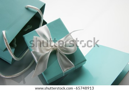 small turquoise box tied with a white ribbon and bag