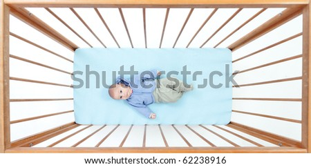 small, two months baby boy lying in a crib (cot)