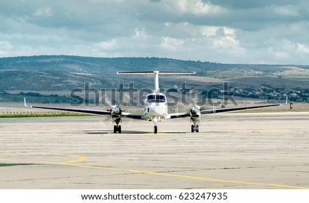 Small two propeller engine jet aircraft taxiing on the apron after landing, rotating propellers. Travel concept.