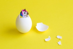 Small unicorn coming out from egg abstract.