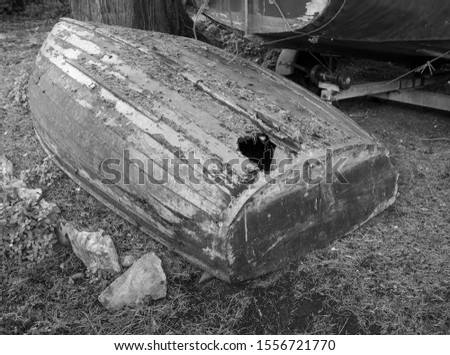 Small upturned wooden boat with damage