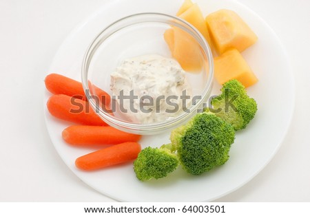 Small veggie plate of baby carrots, broccoli, cantaloupe and garlic dip.  White plate on white background. Clean and simple.