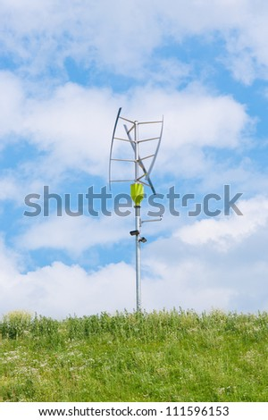 small vertical axis wind turbine on a green hill