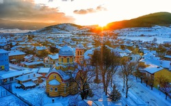 Small village in Bulgaria drone picture. Sunset time. Orthodox church in foreground.