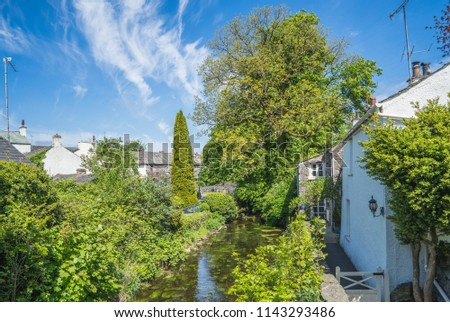 Small village of Cartmel, several cottages alongside a small river. Trees and blue sky.  Stock photo ©