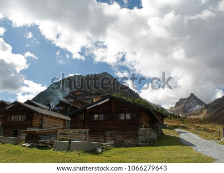 small village of old wooden hut, cabin, chalets, typical of Valais, snow covered mountains, autumn colors, sun, clouds, forest, travel, above city of Goppenstein, Bern, Alps, Switzerland #1066279643