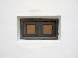 Small vintage wooden window with grate in white lime wall. Old window on white cement wall. Architecture and construction detail. Masonry pattern.