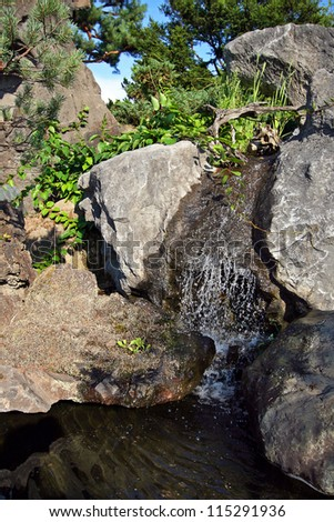 Small waterfall among the rocks in japanese garden.