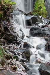 Small waterfall downwards rocks a frosty day in winterseason.
