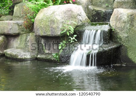 Small waterfall in public tropical garden.