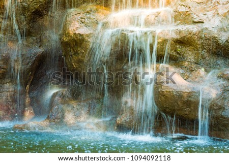 Small waterfall in the garden at home close up.