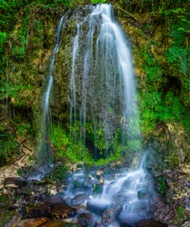 Small waterfall in the green forest . Smooth clean water.
