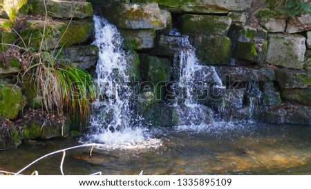 Small waterfall, in the lake in Förch, in the public park of castle Favorite