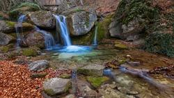 small waterfall on autumn mountain river