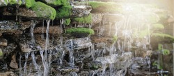 Small waterfall stone pattern with moss strains and running water panorama background, light effect, selective focus on stone.