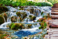 Small waterfall, water stream between rocks and grass