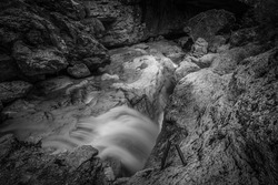Small waterfalls of transparent water in a rocky gorge, Dolomiti Bellunesi National Park, Dolomites, Italy. Long exposure and black and white photo