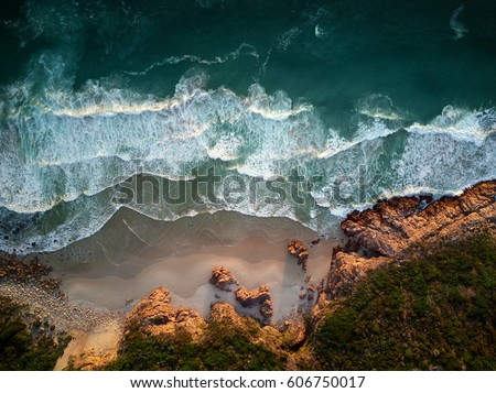 Small waves repeatedly crashing on small sandy shore bay beach with rough rocky coastline, aerial photography overhead #606750017
