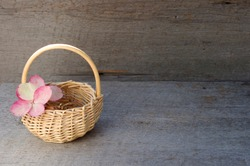 small whicker basket with pink hydrangea flower on side on rustic wooden background with copy space