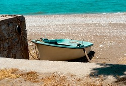 Small white and blue wooden boat on the sand shore at coast tighten with old rusty chain to the stone wall, sea water on background