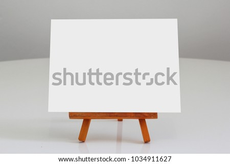 Small white blank banner on wooden canvas stand glossy table