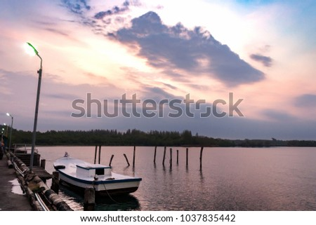 Stock Photo Small white boat parked at the pier in the morning Twilight sea sky In the rain with dense clouds.