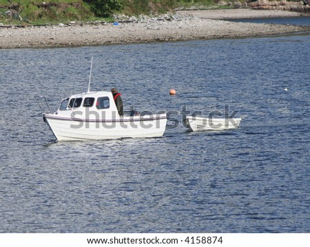 small white boat pulling dingy - stock photo