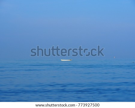Small white boat sailing alone in the  blue sea. and  beautiful blue sky For use as background #773927500