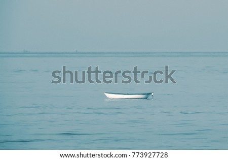 small white boat sailing alone in the  blue sea. and  beautiful blue sky For use as background #773927728