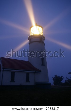 Small white Cape Blanco lighthouse in Oregon, USA at night with light beams filling the sky at dusk. Provides safety against danger for ships in the ocean. / Illuminated Lighthouse at Night