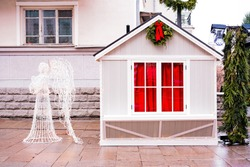 Small white Christmas house with red drapes and Christmas wreath and art installation of angel made from small light lamps. Xmas. Celebration. Holidays. Illuminated decoration. Garland