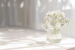 Small white daisies in a glass jar on a white table.