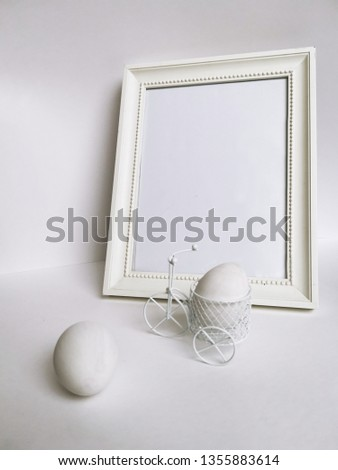 Small white decorative tricycle. Bicycle made of thin metal rods. White Easter eggs and white wooden frame. #1355883614