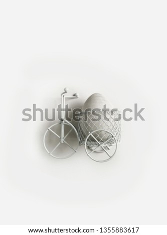 Small white decorative tricycle. Bicycle made of thin metal rods. White Easter eggs and white wooden frame. #1355883617
