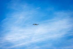 Small white drone flying on blue sky with clouds and copy space, photography.