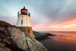 Small, white, granite built Castle Hill Lighthouse sits on the rocky coastline of Newport, Rhode Island on the Atlantic coast of New England. Sunset with waves slowly rushing across the rocks.