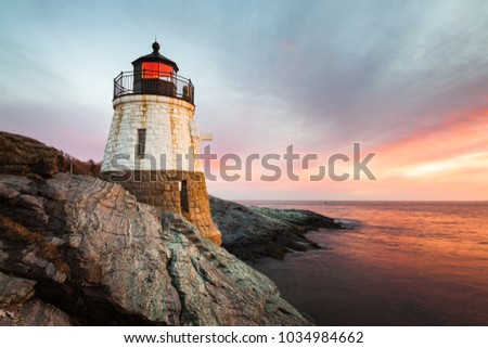 Small, white, granite built Castle Hill Lighthouse sits on the rocky coastline of Newport, Rhode Island on the Atlantic coast of New England. Sunset with waves slowly rushing across the rocks. #1034984662