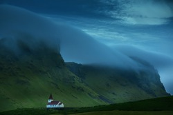 small white house,  church on the slope of the mountain. Clouds and clouds descending from the mountains, gloomy atmosphere, minimalism, a secluded landscape. Iceland.