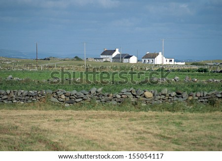 Small white houses in Ireland countryside and view of green fields, Europe