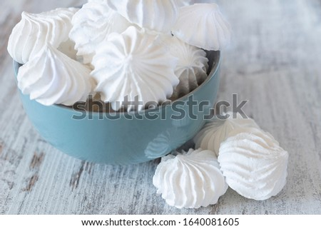 Small white meringues in the blue ceramic bowl and three meringues nearby with reflection in the bowl on the wooden rustic table Сток-фото ©