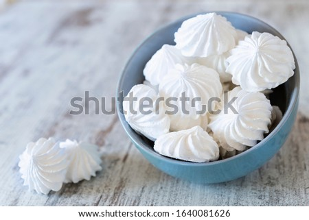 Small white meringues in the blue ceramic bowl and two meringues nearby on the wooden rustic table ストックフォト ©