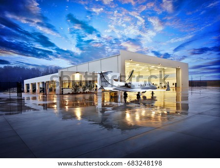 Small white private jet on wet runway at night in front of airplane hanger