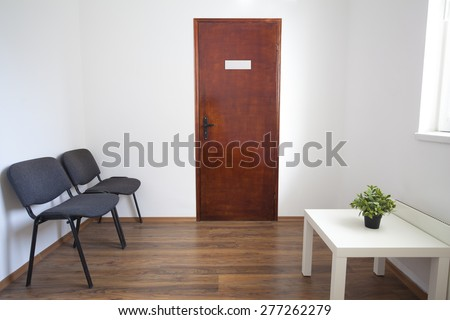 Small white waiting room without people. A doctor, dentist or other medical practitioner provides this room for the use of people who are waiting to be seen.