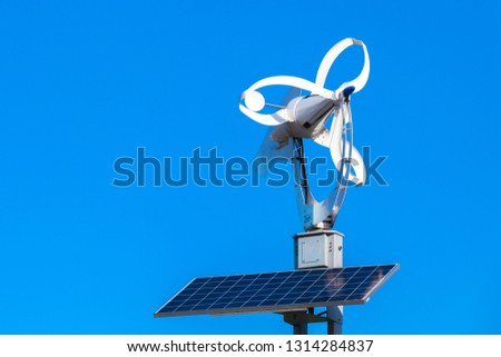 Small white wind turbine and solar battery panel over blue sky background #1314284837