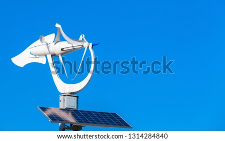 Small white wind turbine with solar battery panel over blue sky background #1314284840