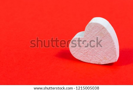 Small white wooden heart on red bright background #1215005038