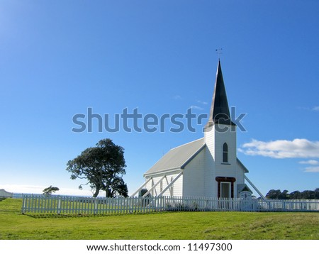 small white wooden protestant church with a blue sky