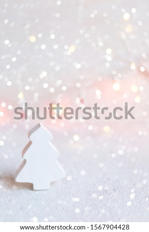 Small white wooden tree on abstract christmas lights background. Greeting card template christmas and New Year with copyspace for text.