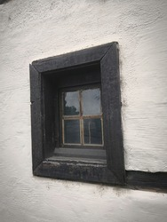Small window in black frame in the old half-timbered white house with dark wood stud. Part of long-standing old-fashioned house with quartered window in dark wood frame. Idea for architectural concept