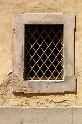 Small window with crosshatch metal grill in the wall of a building in Florence, Italy